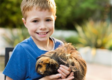 Smiling boy holding guinea pig outdoors Stock Photo - Premium Royalty-Free, Code: 6113-06720864