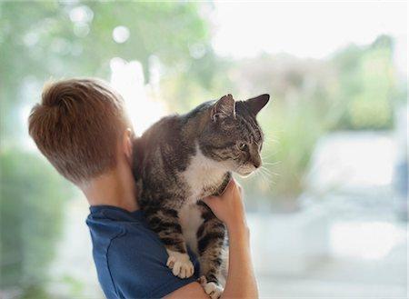 pet - Boy holding cat indoors Stock Photo - Premium Royalty-Free, Code: 6113-06720866
