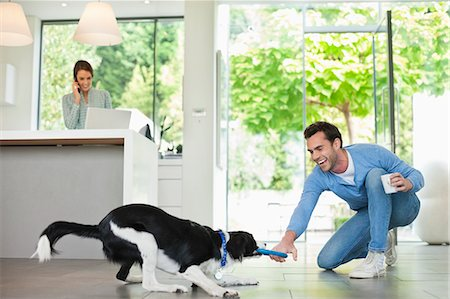 Man playing with dog in kitchen Stock Photo - Premium Royalty-Free, Code: 6113-06720870
