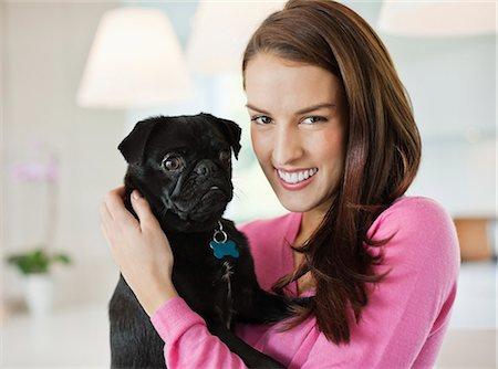 pvg - Smiling woman holding dog indoors Stock Photo - Premium Royalty-Free, Code: 6113-06720872