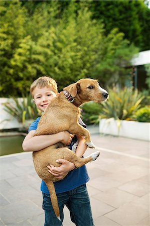 Smiling boy holding dog outdoors Stock Photo - Premium Royalty-Free, Code: 6113-06720883