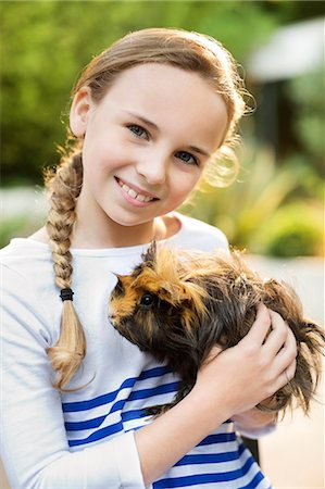 Smiling girl holding guinea pig outdoors Stock Photo - Premium Royalty-Free, Code: 6113-06720881