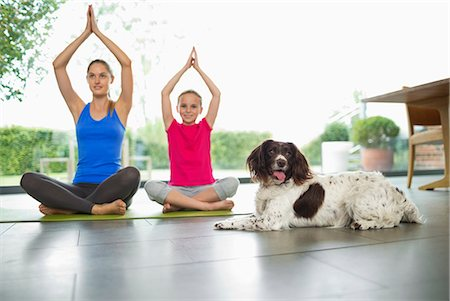 preteen girls stretching - Dog sitting with mother and daughter practicing yoga Stock Photo - Premium Royalty-Free, Code: 6113-06720886
