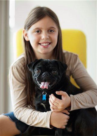 pvg - Smiling girl holding dog indoors Stock Photo - Premium Royalty-Free, Code: 6113-06720949