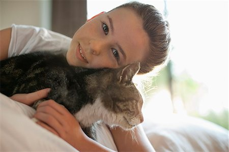 preteen girl pussy - Girl petting cat on bed Stock Photo - Premium Royalty-Free, Code: 6113-06720984