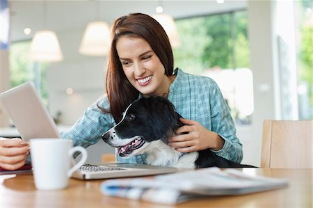 Woman with dog on lap using laptop Stock Photo - Premium Royalty-Free, Code: 6113-06720989