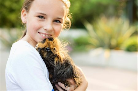 Smiling girl holding guinea pig outdoors Stock Photo - Premium Royalty-Free, Code: 6113-06720916