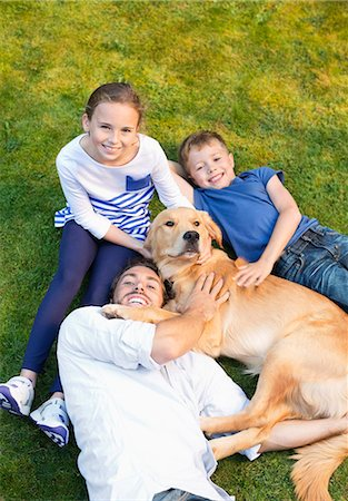 preteen family - Family relaxing with dog on lawn Stock Photo - Premium Royalty-Free, Code: 6113-06720919