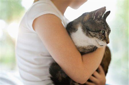 preteen girl pussy - Girl holding cat indoors Stock Photo - Premium Royalty-Free, Code: 6113-06720923