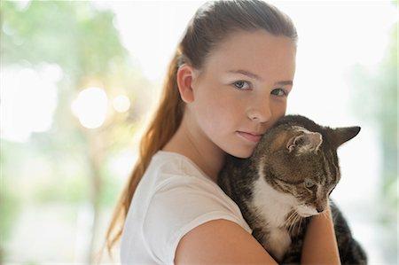 preteen girl pussy - Girl holding cat indoors Stock Photo - Premium Royalty-Free, Code: 6113-06720939