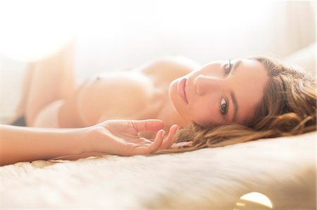 Nude woman laying on bed Stock Photo - Premium Royalty-Free, Code: 6113-06721057