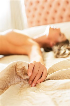 female nude breast sexy - Nude woman gripping sheets on bed Stock Photo - Premium Royalty-Free, Code: 6113-06721064