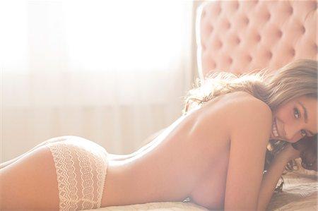 Smiling woman wearing panties on bed Stock Photo - Premium Royalty-Free, Code: 6113-06721027
