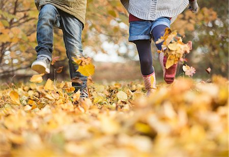 Children walking in autumn leaves Stock Photo - Premium Royalty-Free, Code: 6113-06721144