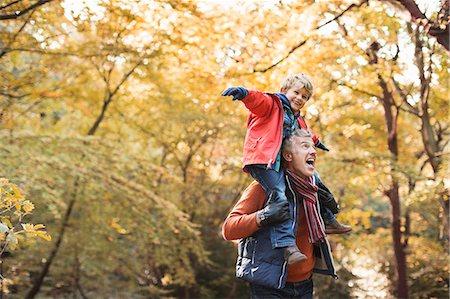 Older man carrying grandson on shoulders Stock Photo - Premium Royalty-Free, Code: 6113-06721145