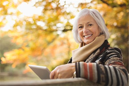 people sitting on bench - Older woman using tablet computer outdoors Stock Photo - Premium Royalty-Free, Code: 6113-06721171