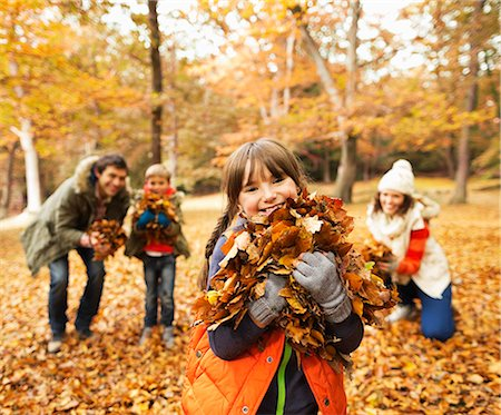Family playing in autumn leaves Stock Photo - Premium Royalty-Free, Code: 6113-06721183