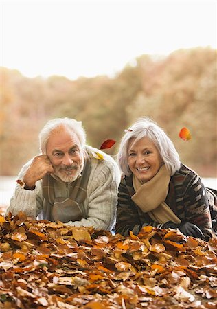 Older couple laying in autumn leaves Stock Photo - Premium Royalty-Free, Code: 6113-06721184