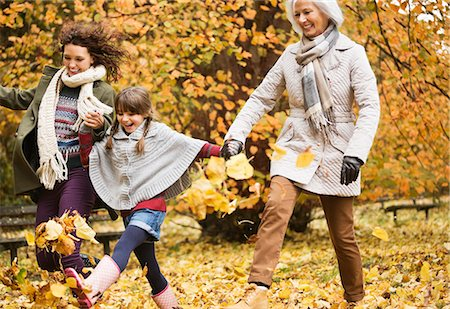 Three generations of women playing in autumn leaves Stock Photo - Premium Royalty-Free, Code: 6113-06721198
