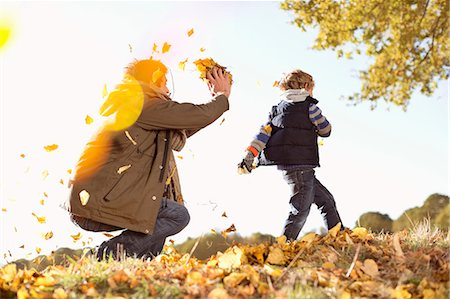 fall - Father and son playing in autumn leaves Stock Photo - Premium Royalty-Free, Code: 6113-06721135