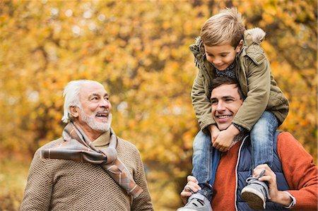 Three generations of men smiling in park Stock Photo - Premium Royalty-Free, Code: 6113-06721275