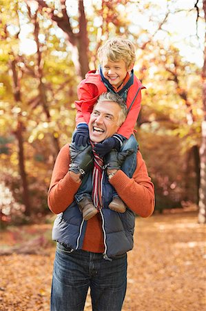 fall - Older man carrying grandson on shoulders in park Stock Photo - Premium Royalty-Free, Code: 6113-06721232