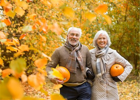 Older couple carrying pumpkins in park Stock Photo - Premium Royalty-Free, Code: 6113-06721301