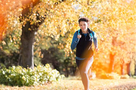 Woman running in park Stock Photo - Premium Royalty-Free, Code: 6113-06721324