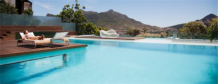 pool - Woman sunbathing on lounge chair next to luxury swimming pool with mountain view Stock Photo - Premium Royalty-Free, Code: 6113-06898822