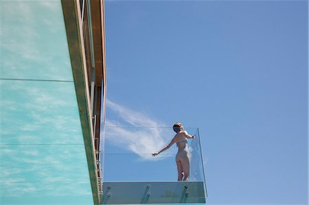 Woman with arms outstretched on modern balcony Stock Photo - Premium Royalty-Free, Code: 6113-06898829