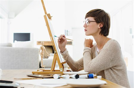 Woman painting on easel at table Stock Photo - Premium Royalty-Free, Code: 6113-06898946