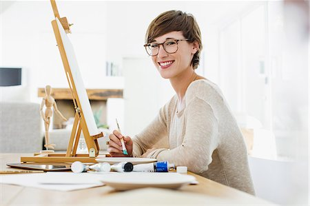 painter - Portrait of smiling woman painting at easel on table Stock Photo - Premium Royalty-Free, Code: 6113-06898956