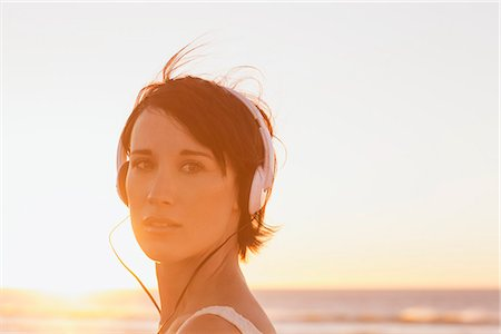 pretty - Close up portrait of confident woman wearing headphones at beach Stock Photo - Premium Royalty-Free, Code: 6113-06898962