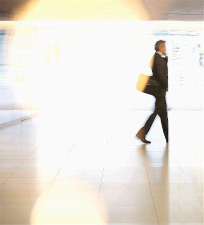 Businessman walking in lobby Stock Photo - Premium Royalty-Free, Code: 6113-06898991