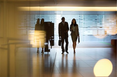 silhouettes - Businessman and businesswoman walking in lobby Stock Photo - Premium Royalty-Free, Code: 6113-06898999