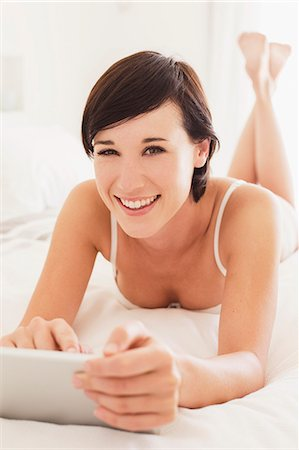 short hair - Portrait of smiling woman using digital tablet in bed Stock Photo - Premium Royalty-Free, Code: 6113-06898923