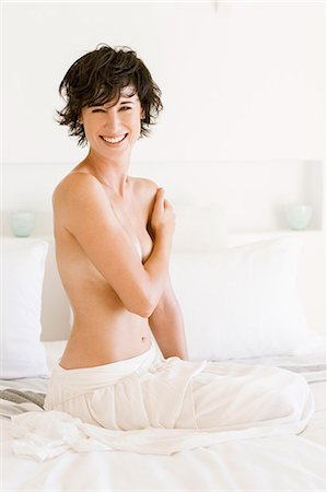 female nude breast sexy - Portrait of smiling woman covering breasts in bed Stock Photo - Premium Royalty-Free, Code: 6113-06898927