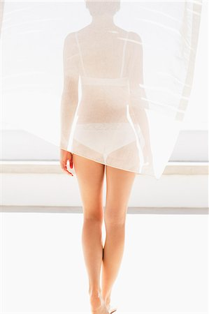 Rear view of woman in bra and underwear behind curtain Stock Photo - Premium Royalty-Free, Code: 6113-06898926
