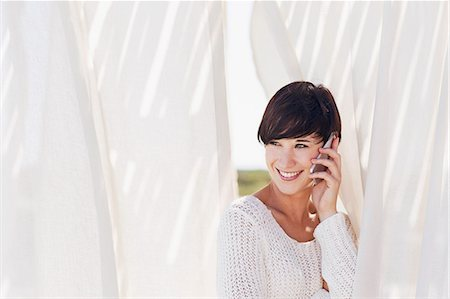 Smiling woman talking on cell phone Stock Photo - Premium Royalty-Free, Code: 6113-06898934