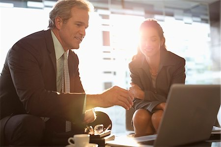 Businessman and businesswoman using laptop in lobby Stock Photo - Premium Royalty-Free, Code: 6113-06899057