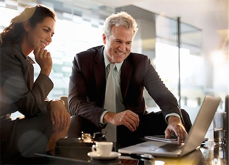 Smiling businessman and businesswoman using laptop in lobby Stock Photo - Premium Royalty-Free, Code: 6113-06899059