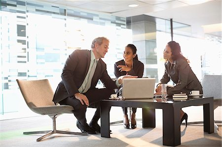 Business people with laptop meeting in lobby Stock Photo - Premium Royalty-Free, Code: 6113-06899060