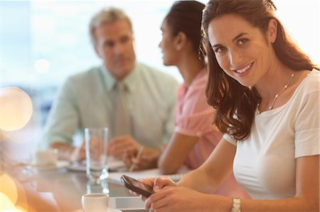 Portrait of smiling businesswoman with cell phone in meeting Stock Photo - Premium Royalty-Free, Code: 6113-06899073
