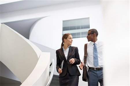 Businessman and businesswoman talking on modern staircase Stock Photo - Premium Royalty-Free, Code: 6113-06899084