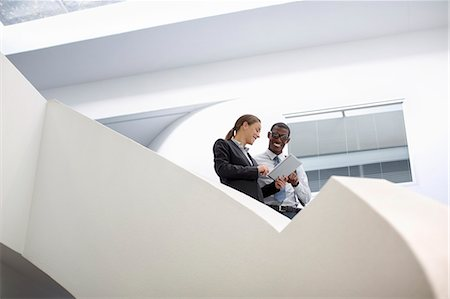 Businessman and businesswoman using digital tablet on modern staircase Stock Photo - Premium Royalty-Free, Code: 6113-06899099