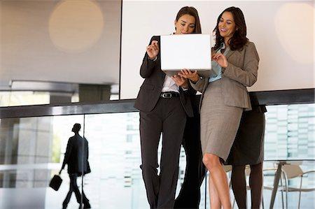 Businesswomen using laptop in lobby Stock Photo - Premium Royalty-Free, Code: 6113-06899015