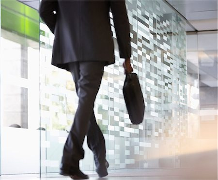 Businessman with briefcase walking in lobby Stock Photo - Premium Royalty-Free, Code: 6113-06899023