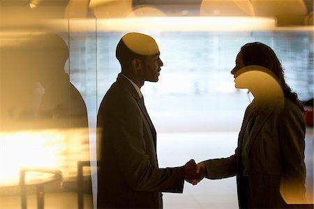 partnership - Businessman and businesswoman handshaking in lobby Stock Photo - Premium Royalty-Free, Code: 6113-06899030