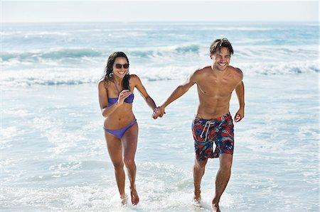 partnership - Couple running in ocean surf Stock Photo - Premium Royalty-Free, Code: 6113-06899181