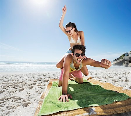Woman piggybacking enthusiastic man on beach Stock Photo - Premium Royalty-Free, Code: 6113-06899182
